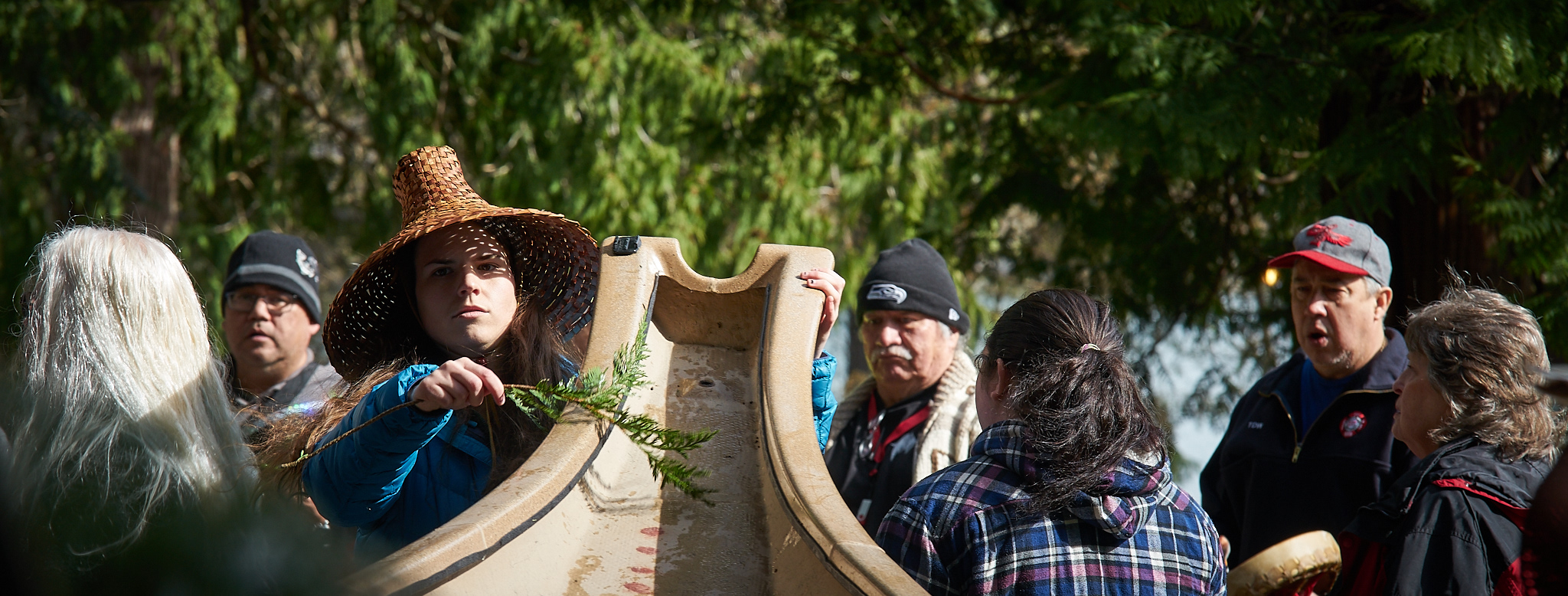 Kelly Hall brushes a Samish canoe with cedar during an annual ceremony to waken the canoes after winter.